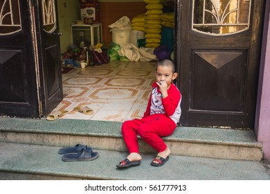 Hanoi, Vietnam - 13 November 2016: little boy sitting at the stairs of his house.