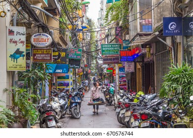 HANOI, VIETNAM,  19TH MARCH 2017: A view along streets of Hanoi during the day. Buildings, shop signs, parked motorbikes and people can be seen.
