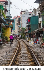 HANOI, VIETNAM - 19TH MARCH 2017: A view along train tracks running through the city of Hanoi. The outside of buildings and people can be seen along the side.