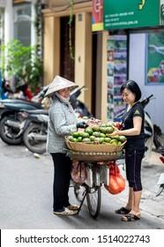 Hanoi, Vietnam - 20.05.2019: Traditional street fruit seller on bicycle at Hanoi, Vietnam. Woman selling avocado at street of Vietnam.