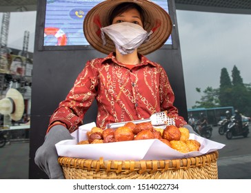Hanoi, Vietnam - 20.05.2019: Woman with pollution mask selling traditional vietnams food at the street of Hanoi.