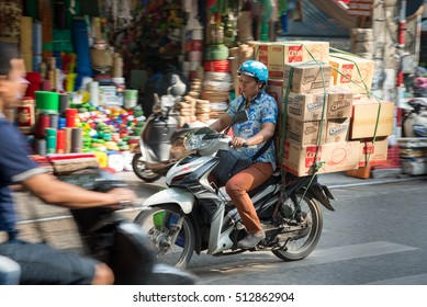 Hanoi, Vietnam - 21 October 2016: Typical vietnamese street scene - overloaded scooter making deliveries in the market district