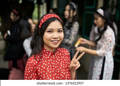 Hanoi, Vietnam - 24 February 2019: smiling asian girl in a vietnamese red dress with flower prints and headband is showing V sign gesture on the blurred background of women on the street. Editorial.