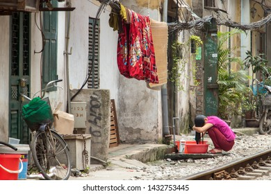 HANOI, VIETNAM, APR 21 2019, A woman washes her hair at the railroad track in the city center
