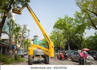 Hanoi, Vietnam - Apr 24, 2016: Mechanical platform to make tree pruning on Dinh Tien Hoang street, center of Hanoi capital