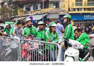 Hanoi, Vietnam - Apr 9, 2017: Vietnamese Grab bike riders waiting for passenger on a street. Grab is a popular app for taxi service in Southeast Asia.