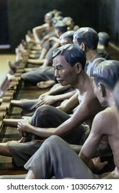 HANOI, VIETNAM. APRIL 10, 2016: Models of detained prisoners by lock their foot ankle on something like wooden console at Hoa Lo Prison Museum in Hanoi, Vietnam.