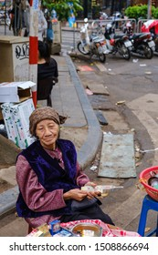 Hanoi, Vietnam - April 10 2019. Portrait of a woman selling cigarettes and water on the street wearing typical clothes from Vietnam. Street goods on the street is quiet common in South East Asia.