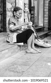 Hanoi VIetnam, April 14 2017 : Black and White, lonely old woman eating and sit on roadside at Hanoi city