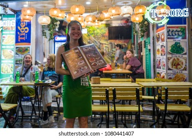 Hanoi, Vietnam - April 17, 2018: Waitress in the rain in Bia Hoi corner smiles at camera in Hanoi.