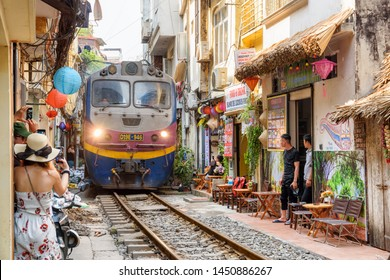 Hanoi, Vietnam - April 18, 2019: Incredible view of train passing through a narrow street, the Hanoi Old Quarter. Tourists taking pictures of the train. The Hanoi Train Street is a popular attraction.