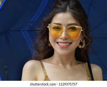 HANOI, VIETNAM - APRIL 2, 2018: Attractive Vietnamese woman with butterfly-shaped yellow sunglasses, smiles and poses for the camera under a blue sun umbrella, on April 2, 2018.
