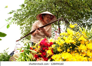 HANOI, VIETNAM - APRIL 21: Unidentified flower vendor at the flower small market on April 21, 2012 in Hanoi, Vietnam. This is a small market for retail florists and street vendors.