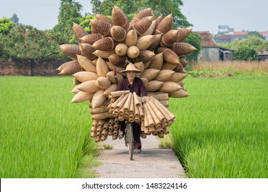 Hanoi, Vietnam - August 10, 2019 : Old men riding bicycles selling wicker craftsman making traditional bamboo fish trap or weave in Thu Sy trade village, Hung Yen town Hanoi, Vietnam