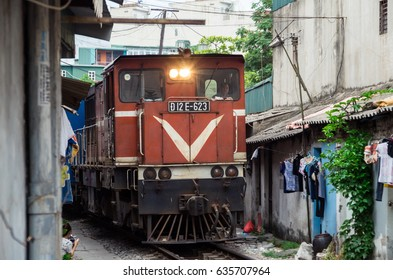 Hanoi, Vietnam - August 16, 2015: locals live their life on and around the train line passing between buildings in the Old Quarter of Hanoi.