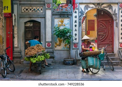 Hanoi, Vietnam - August 21, 2017: Street vendors selling fruits from their bicycles and scooters