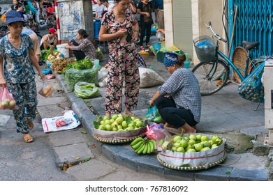 Hanoi, Vietnam - August 21, 2017: Street market with farmers selling fruits and vegetables on the kerb