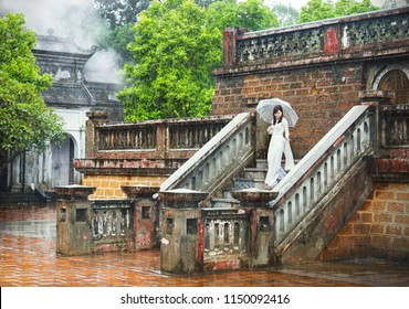 Hanoi, Vietnam August 28, 2016: A girl in traditional attire (ao dai) visits the historic ruins in the rain.