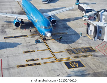 HANOI, VIETNAM - August 7, 2019 : Vietnam Airlines aircraft prepares for docking with landing sleeve and loading air cargo containers before flight at Noi Bai international airport in Hanoi, Vietnam.