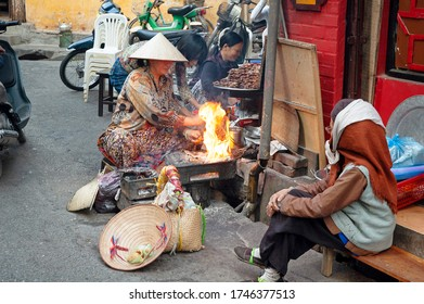 Hanoi / Vietnam - Dec 13 2006: A woman cooking meat for sale on the streets of Hanoi, Vietnam