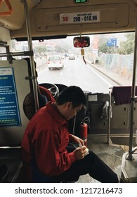 HANOI, VIETNAM - DECEMBER 30, 2017:  a bus conducting sitting near the driver's front console inside the city bus