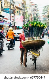 Hanoi, Vietnam - December 31, 2016: The street vendors in Hanoi, Vietnam. Woman selling flowers in the early morning on a busy street.