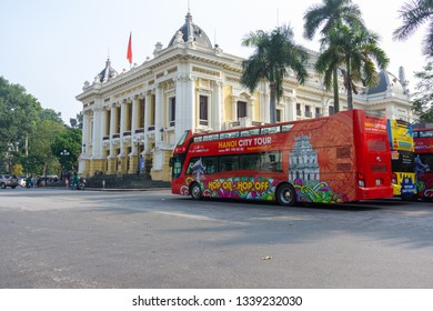 Hanoi, Vietnam - Feb 18, 2019: Luxury city tour bus on Hanoi street with Hanoi Opera House on background