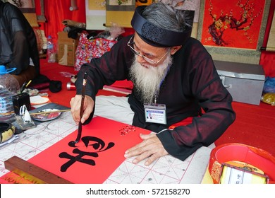 HANOI, VIETNAM, FEB 4, 2017: Old master is writing ancient letter for everyone in lunar new year in Hanoi, Vietnam. This is a tradition of vietnamese people in lunar new year