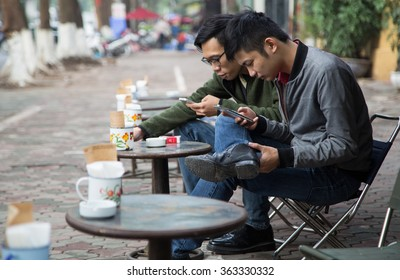 Hanoi, Vietnam - Jan 17, 2016: Asian people drinking coffee on the sidewalk at a franchised Cong coffee shop in Hanoi capital city.