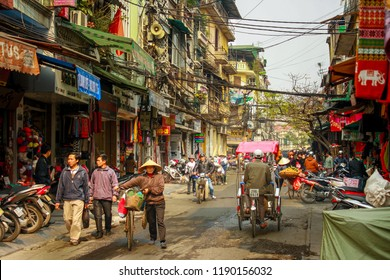 Hanoi, Vietnam - Jan 2014: People, bicycles and tuk tuks on a busy, bustling street in the old town of Hanoi, in northern Vietnam