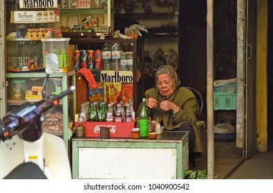 HANOI, VIETNAM – JANUARY 14, 2002: lady selling drinks in the city old quarter. The shops create in the city a great atmosphere.