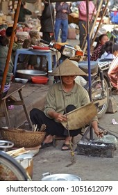 HANOI, VIETNAM – JANUARY 14, 2002: lady cooking food in a street restaurant in the city old quarter. The place has a great humanity.
