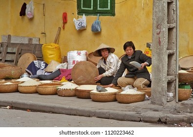 HANOI, VIETNAM – JANUARY 14, 2002: lady selling rice along the street. Typical example of the life in the city old quarter.