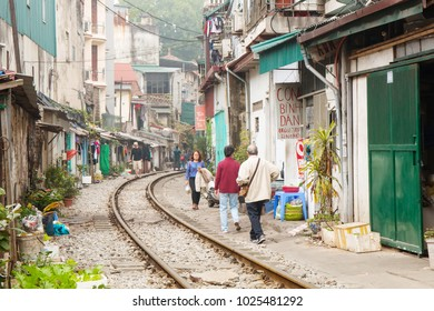 Hanoi, Vietnam - January 20, 2018: Daily life of Hanoi at Old Quarter. Railroad tracks passing between buildings on a street in the center of Hanoi in Vietnam