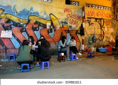 HANOI, VIETNAM - JANUARY, 2016 : Unidentified youth people are eating at street food vendors in Hanoi's Old Quarter at night. Lifestyle of Vietnam.