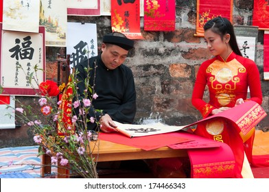 HANOI, VIETNAM, JANUARY 28: Old master write ancient letters for a girl in Aodai costume on January 28, 2014 in Hanoi, Vietnam. This is a tradition of vietnamese people in lunar new year