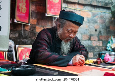 HANOI, VIETNAM, JANUARY 28: Old master is writing ancient letter for everyone in lunar new year on January 28, 2014 in Hanoi, Vietnam. This is a tradition of vietnamese people in lunar new year