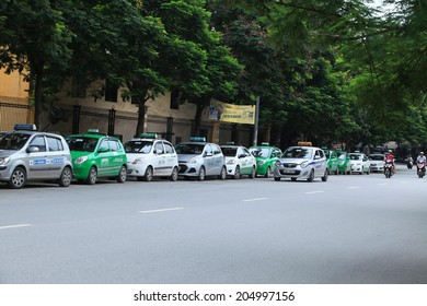 HANOI, VIETNAM - JUL 12, 2014: Taxi-cabs parking on the side of a street in Hanoi capital, Vietnam. Traffic is one of the most serious matter in the country with many vehicles on narrow streets.