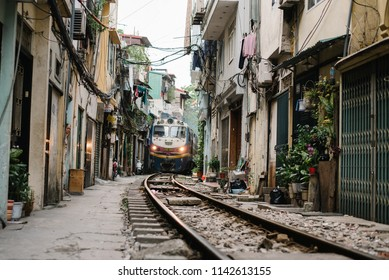 Hanoi / Vietnam - July 11th 2018: A passenger train crosses the city on a narrow street in Le Duan neighborhood in Hanoi