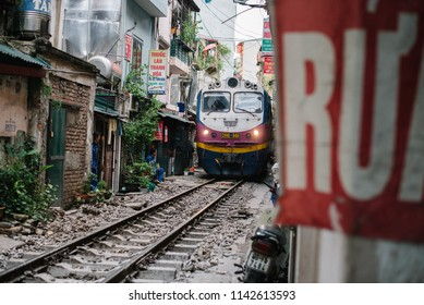 Hanoi / Vietnam - July 16th 2018: A passenger train crosses the city on a narrow street in Le Duan neighborhood in Hanoi