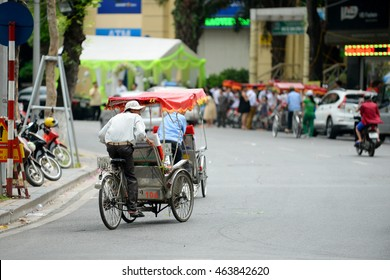 Hanoi, Vietnam - July 2, 2016:  Cyclo beside Hoan Kiem lake. Cyclo is the tourist's favorite vehicle transportation and the ancient city tour by cyclo around is very popular with tourists.