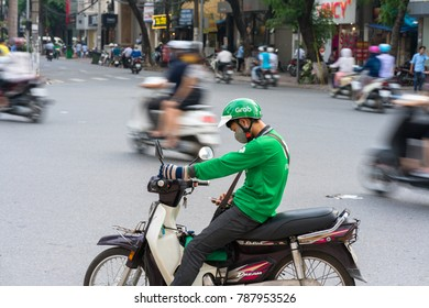 Hanoi, Vietnam - July 7, 2017: Grab motorbike driver waiting for customer on Ba Trieu street. Entered Vietnam in 2014, Grab growing fast due to cheap fare and safer than traditional motorbike taxi