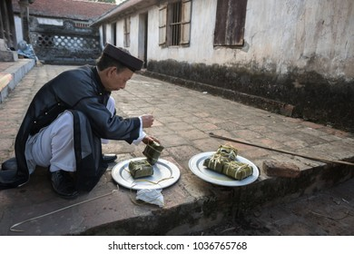 Hanoi, Vietnam - Jun 22, 2017: The man take Chung cake out of cooking pot at So village, Quoc Oai district. Square glutinous rice cake, Vietnamese lunar new year food