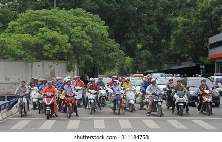 HANOI, VIETNAM - JUNE 2, 2015: people on crossroad are waiting the green signal of traffic light