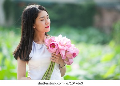 Hanoi Vietnam June 25 2017 Vietnamese girl wearing pink color traditional Vietnamese bodice (simply called a yem).Laughing and picking lotus flowers, The lotus flower is a symbol of Vietnamese culture