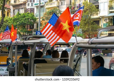 Hanoi, Vietnam - Mar 1, 2019: Electric car with 3 flags of Vietnam, North Korea and US running on street during meeting between Chairman Kim Jong-un and President Donald Trump