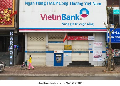 Hanoi, Vietnam - Mar 15, 2015: Exterior front view of Vietinbank in Xa Dan street. It is one of the four largest State-owned commercial banks of Vietnam. A mother pushes baby carriage on sidewalk