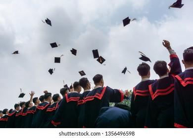 Hanoi, Vietnam - Mar 3, 2019: High school students graduates tossing up hats over blue sky at Hanoi Opera House, Trang Tien street