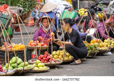 Hanoi, Vietnam - march 01, 2020 : Women selling fruits and vegetables on the street food market of old town in Hanoi, Vietnam