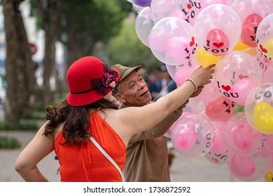 Hanoi, Vietnam - march 01, 2020 : Vietnamese seller offers to buy balloons for a woman on the street in the old town of Hanoi, Vietnam